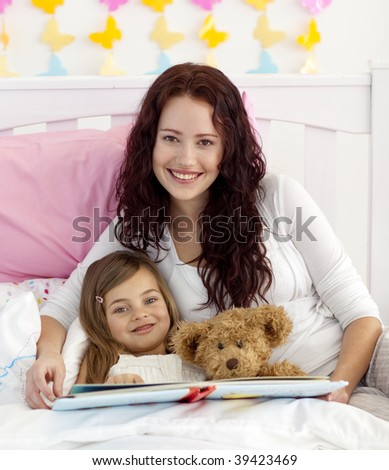 Mother and daughter reading a book together in bedroom