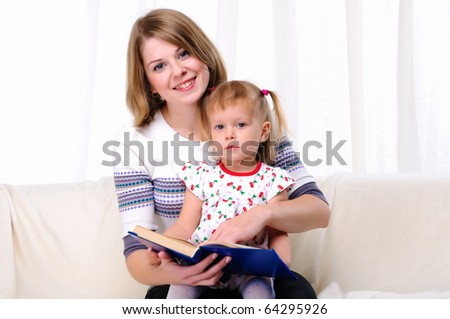 Mother and daughter reading a book together on the couch