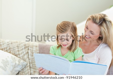 Mother and daughter reading a magazine together - stock photo