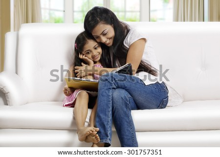 Mother and daughter reading a story book together - stock photo