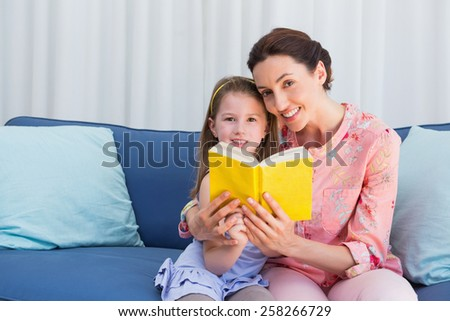 Mother and daughter reading book at home in the living room - stock photo