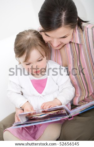 mother and daughter reading book at sofa