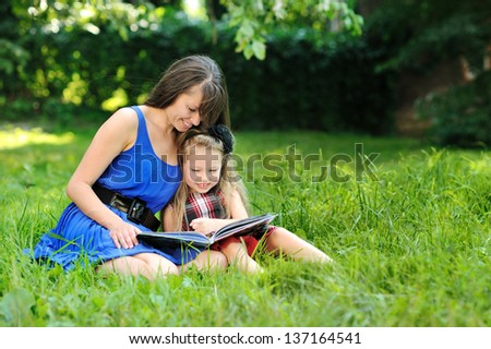 Mother and daughter reading book in a park - stock photo