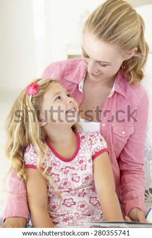 Mother And Daughter Reading Book In Bedroom - stock photo
