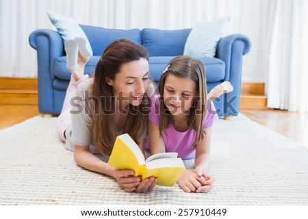 Mother and daughter reading on the floor at home in the living room - stock photo