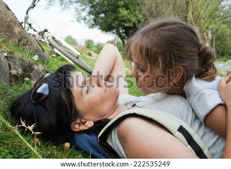 Mother and daughter relaxing after bicycle ride in countryside - stock photo