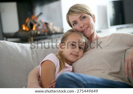 Mother and daughter relaxing by fireplace, laying in couch - stock photo