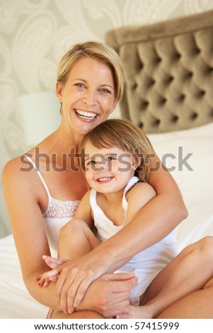 Mother And Daughter Relaxing In Bedroom - stock photo