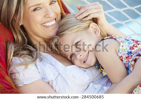 Mother And Daughter Relaxing In Garden Hammock Together - stock photo