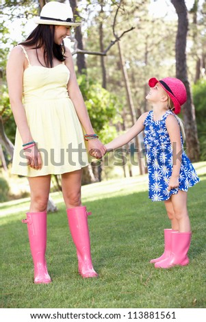 Mother And Daughter Relaxing In Summer Garden - stock photo