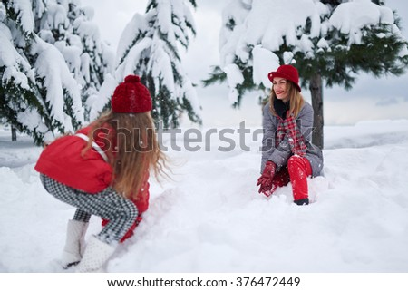 mother and daughter resting in a park in winter