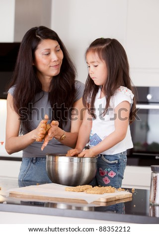 Mother and daughter rolling cookie dough together in kitchen - stock photo