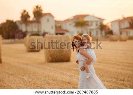 mother and daughter run on field in summer at sunset, in the background a haystack, family happiness - stock photo