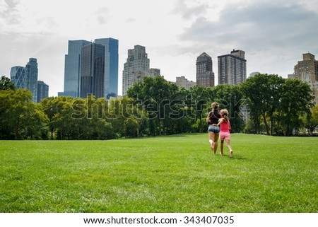 mother and daughter running away on the grass in the park - stock photo
