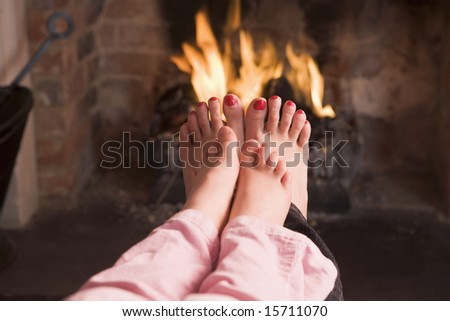 Mother and daughter's Feet warming at a fireplace - stock photo