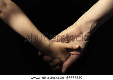 Mother and daughter's hands on black background. - stock photo