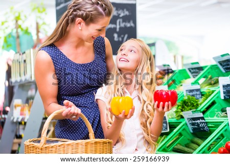 Mother and daughter selecting vegetables while grocery shopping in organic supermarket  - stock photo