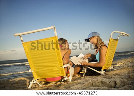 Mother and daughter share a reading book while sitting beach chairs. Horizontal shot. - stock photo