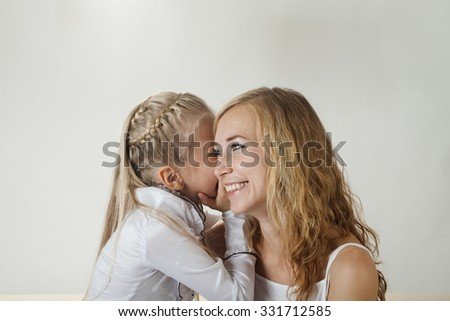 Mother and daughter sharing a secret indoors - stock photo