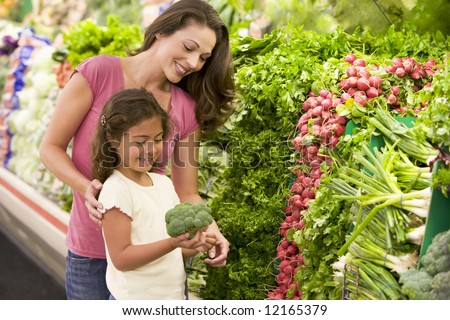Mother and daughter shopping for fresh produce in supermarket - stock photo