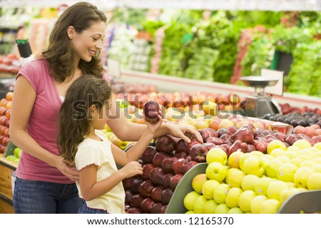 Mother and daughter shopping for fresh produce in supermarket [approx. 7 years old] - stock photo