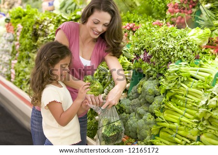 Mother and daughter shopping for produce in supermarket - stock photo