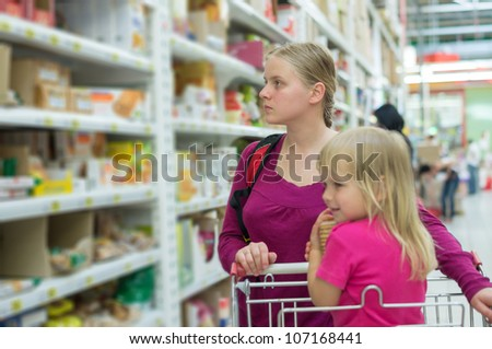 Mother and daughter shopping in cookies section in supermarket