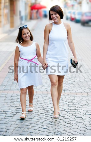 Mother and daughter shopping in mall - stock photo