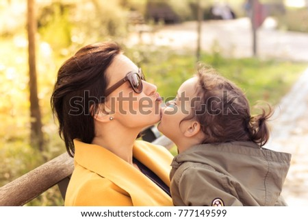 Mother and daughter showing affection towards each other. Little girl is kissing her mother on the chin.