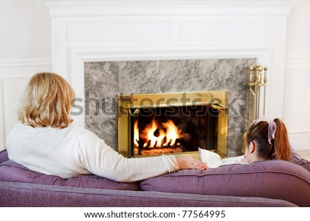 Mother and daughter sit on the sofa  to read by the fire