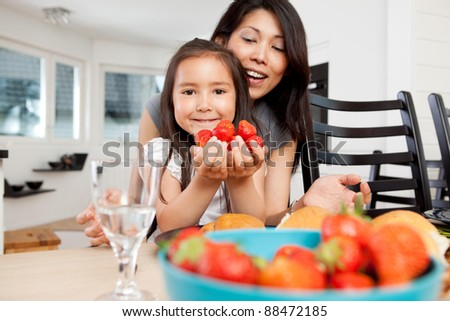 Mother and daughter sitting at table in kitchen with handful of strawberries - stock photo