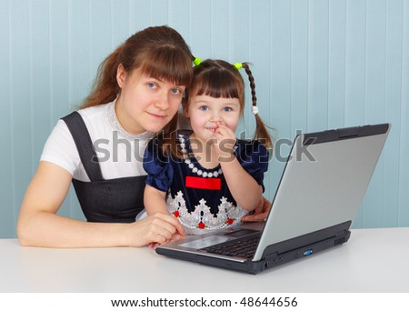 Mother and daughter sitting at the table with a computer