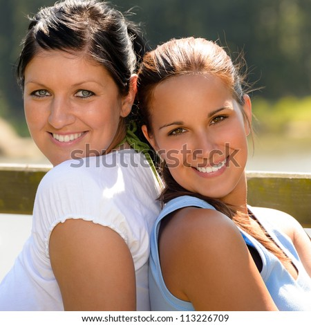 Mother and daughter sitting back to back teen smiling relaxing