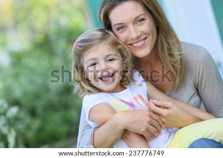 Mother and daughter sitting by house front door - stock photo