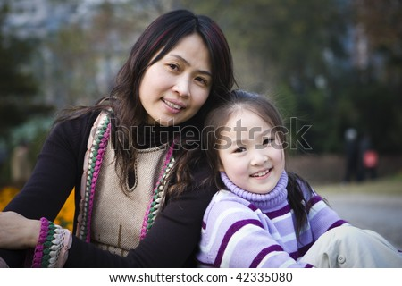 mother and daughter sitting in a city park, shanghai, china - stock photo