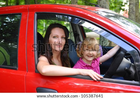 Mother and daughter sitting in a red car