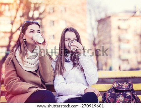 Mother and daughter sitting in autumn or spring in the park on a bench outdoors, drink coffee or tea or relax breakfast snack. - stock photo