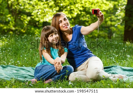 Mother and daughter sitting in nature and talking selfie with camera,Mother and daughter taking a selfie  - stock photo