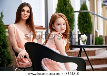 Mother and daughter sitting in street cafe summer time happy family day beautiful cute woman and small little girl in restaurant breakfast holiday morning baby mom buildings fashion dress look - stock photo