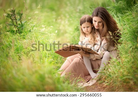 mother and daughter sitting in the meadow and reading book - stock photo