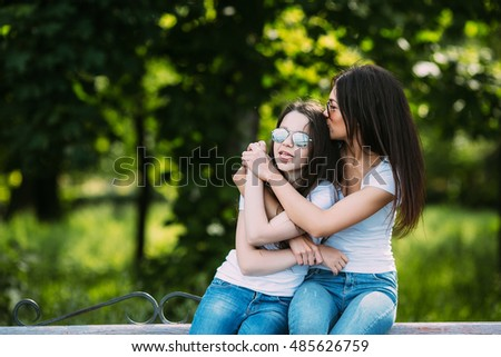 Mother and daughter sitting on a bench in the park