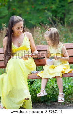 mother and daughter sitting on a bench in the Park and talk - stock photo