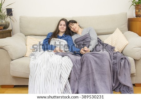 Mother and daughter sitting on a couch holding hands affectionately
