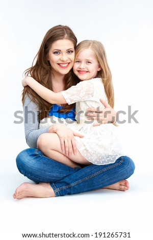 Mother and daughter sitting on a floor. Isolated on white background.