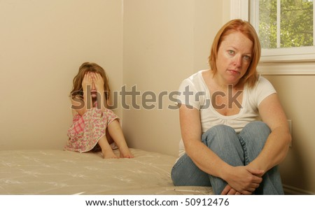 Mother and daughter sitting on a mattress looking sad - stock photo