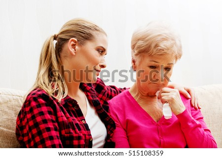 Mother and daughter sitting on couch, daughter comforting her  mother