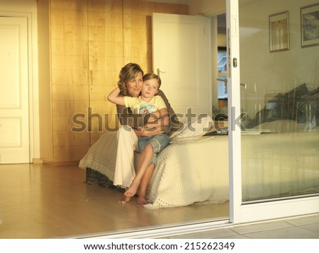 Mother And Daughter 6 8 Sitting On Edge Of Double Bed