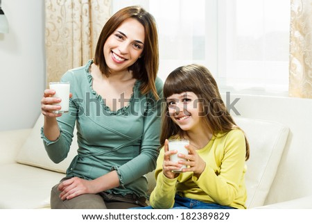 Mother and daughter sitting on sofa at their home and holding glass of milk,Glass of milk for mother and daughter - stock photo