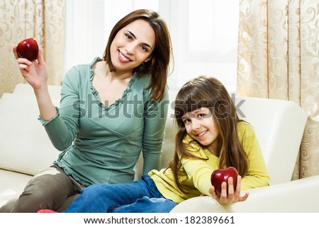 Mother and daughter sitting on sofa at their home and showing apple,they are having healthy snack,Healthy snack for mother and daughter - stock photo
