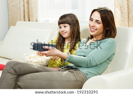 Mother and daughter sitting on sofa at their home,eating popcorn and watching tv,Family time - stock photo